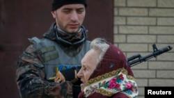 A woman walks past a Ukrainian serviceman as he stands guard in Volnovakha, Donetsk region.