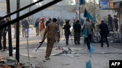 Pakistani security officials inspect the site of a bomb attack in Rawalpindi on January 20.