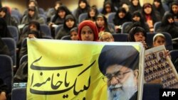 An Iranian girl holds a banner bearing a portrait of supreme leader Ayatollah Ali Khamenei during a campaign meeting of the head of the conservatives grand coalition in February.