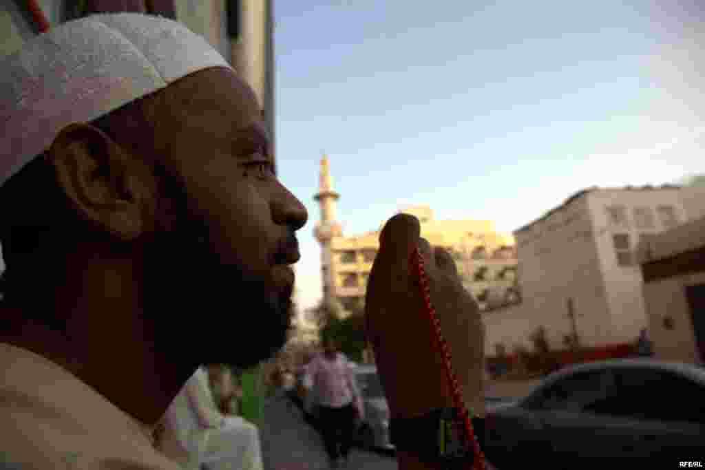 A worker holds prayer beads near a mosque.
