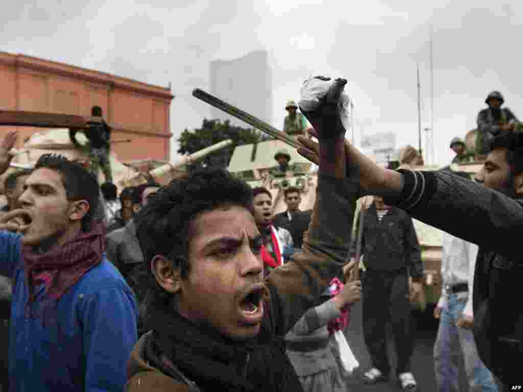 Demonstrators chant slogans in front of army tanks stationed near the National Museum in downtown Cairo on January 29.