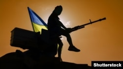 Ukraine – Ukrainian flag, man and machine gun.