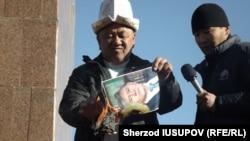 Former regional police chief Abdulla Kapparov burns a portrait of Kyrgyz President Almazbek Atambaev on Osh's central square.
