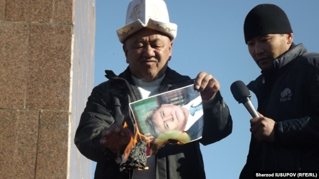 Former regional police chief Abdulla Kapparov burns a portrait of Kyrgyz President Almazbek Atambaev on Osh's central square.