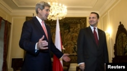 U.S. Secretary of State John Kerry (left) heads into a meeting with Polish Foreign Minister Radoslaw Sikorski in Warsaw on November 5.