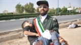 A member of Iran's Islamic Revolutionary Guards Corps (IRGC) carries an injured child.