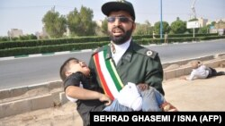 September 22, 2018 in the southwestern Iranian city of Ahvaz shows a member of Iran's Revolutionary Guards Corps (IRGC) carrying an injured child at the scene of an attack on a military parade. Ahvaz Iran