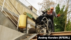 Инвалид пытается спуститься по рельсам