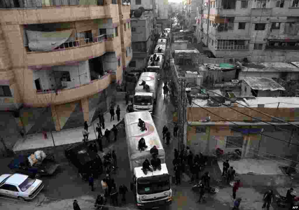 A Red Crescent convoy carrying humanitarian aid arrives in Kafr Batna, in the rebel-held Eastern Ghouta area on the outskirts of the capital Damascus. (AFP/Amer Almohibany)