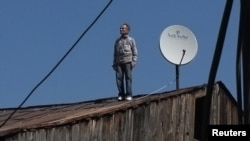 A Georgian man looks on after checking a satellite dish on the roof of a building in Tbilisi in April.