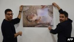 اعضای «سازمان سوری برای قربانیان جنگ» در حال نشان دادن تصویر یکی از قربانیان شکنجه در زندانهای دولتی سوریه. ژنو، مارس ۲۰۱۶