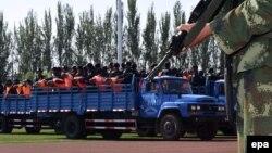 Күдіктілерге үкім шығар сәтте күзетте тұрған қытай полициясы. Құлжа, 27 мамыр 2014 жыл. (Көрнекі сурет)