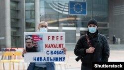 Két ember Brüsszelben egy Navalnij szabadon engedését követelő táblát tart. 2021. január 19.