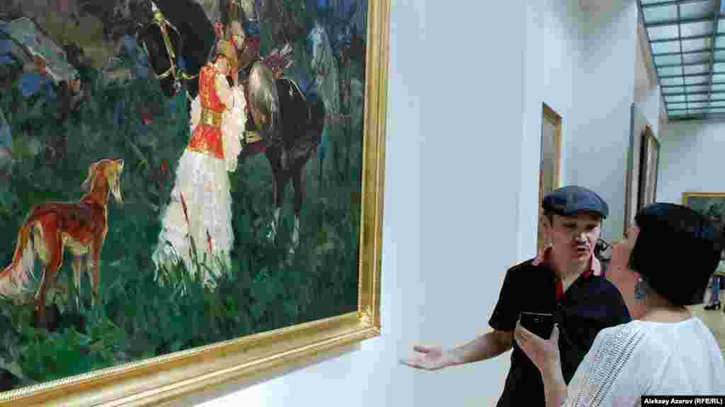 Художник Талгат Тлеужанов перед своей картиной «Прощание» на выставке «Эхо Великой степи».