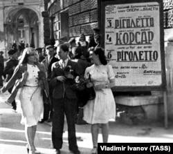 Червень 1944 року. Жителі Одеси, яку було звільнено від нацистів у квітні, перед початком вистави біля будівлі Одеського театру опери і балету. Афіші з назвами вистав – українською мовою