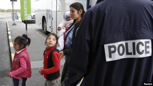 A Roma family walks past a police officer as they arrive at the Lille-Lesquin airport, near Lille in northern France, for their flight to Romania on September 16.