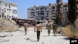 Syrian Army soldiers patrol an area on the outskirts of Aleppo.