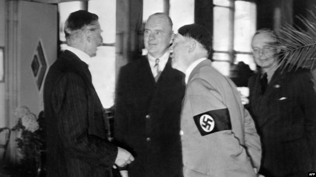 Вождь нацистов Адольф Гитлер беседует с британским премьером Невиллом Чемберленом (слева) в день подписания Мюнхенского соглашения