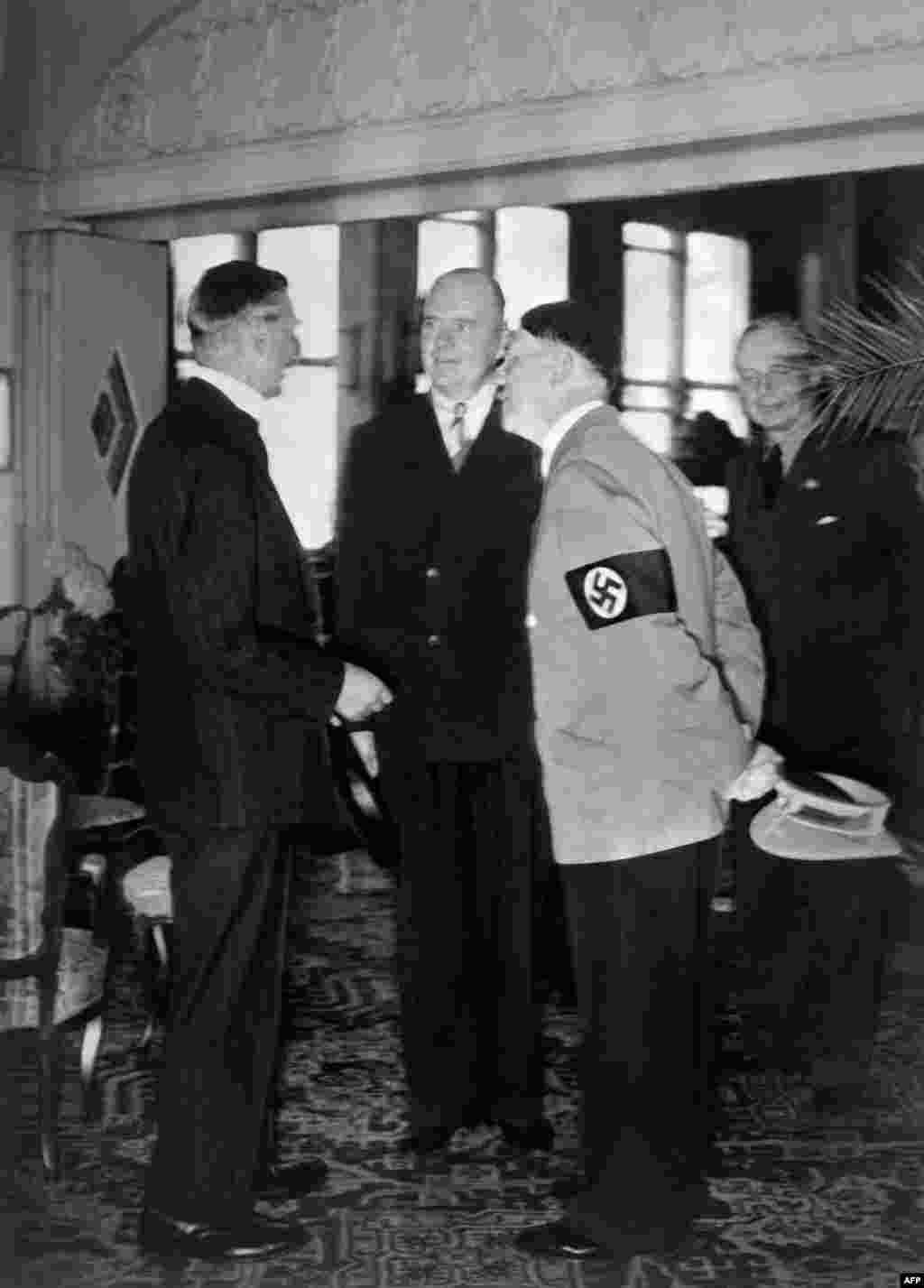 Neville Chamberlain (left) and Adolf Hitler talk with the help of an interpreter as German Nazi Foreign Minister Joachim Von Ribbentrop looks on in the background on September 23, 1938, in Bad Godesburg, Germany.