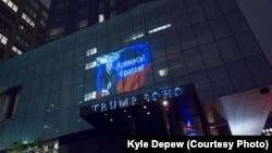 Проекция с изображением президента России, российским флагом и подписью «Крепись, братан» на фасаде гостиницы Trump SoHo.