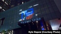 Проекция с изображением президента России, российским флагом и подписью «Крепись, братан» на фасаде гостиницы Trump SoHo