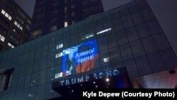 """Проекция с изображением президента России, российским флагом и подписью: """"Крепись, братан"""" - на фасаде гостиницы Trump SoHo. Нью-Йорк, 7 августа 2017 года."""