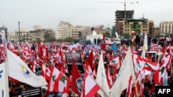 Lebanese wave national flags as they gather in February 2008 to commemorate the third anniversary of the assassination of Lebanese Prime Minister Rafiq Hariri.