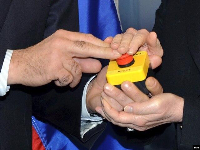 Руки руководителей внешнеполитических ведомств России и США Сергея Лаврова и Хиллари Клинтон - символическая перезагрузка отношений Москвы и Вашингтона. Швейцария, 2009 год