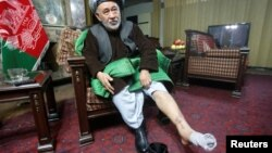 Ahmad Ishchi displays an injury on his leg during an interview at his home in Kabul on December 13.