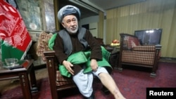 Ahmad Ishchi, who is reported to have been beaten and detained by Afghan Vice President Abdul Rashid Dostum last month, displays an injury on his leg during an interview at his home in Kabul on December 13.