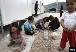 """Дети играют в """"официальном"""" лагере беженцев в окрестностях Афин"""