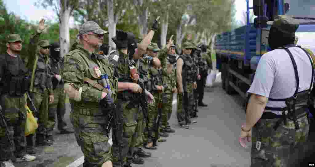 "Pro-Russian separatists of the self-proclaimed ""Vostok Battalion"" preparing to board a truck at a checkpoint on the outskirts of the city of Donetsk on May 25."