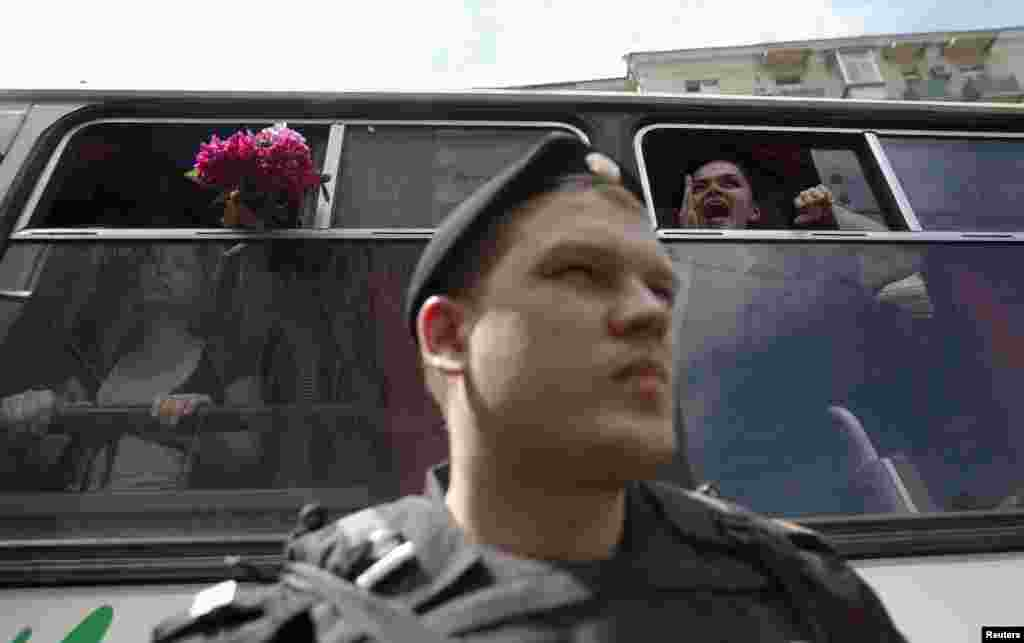 Gay-rights activists shout slogans from a police van after being detained.