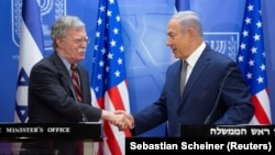 Israeli Prime Minister Benjamin Netanyahu (right) shakes hands with U.S. national-security adviser John Bolton during their meeting at the prime minister's office in Jerusalem on August 20.