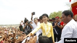 Myanmar's Aung San Suu Kyi shakes hands with supporters in April.