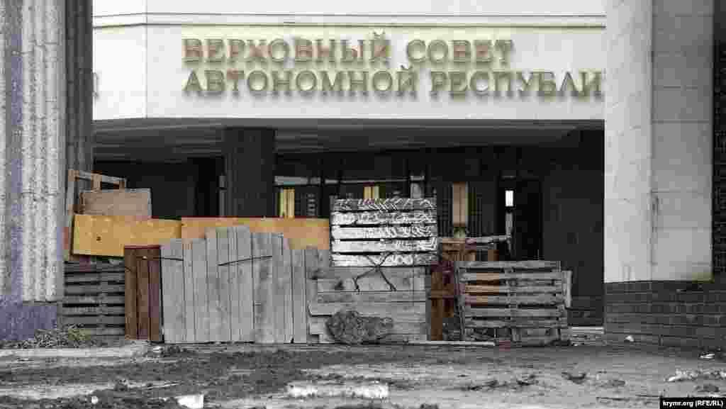В баррикадах у входа в Верховную Раду сделали проходы, но сами заграждения стоят. Что внутри непонятно. Митингующие говорят, что в здание иногда заходят и выходят депутаты крымского парламента. Вооруженных спецназовцев, которые, как теперь, спустя два года, известно, там находились, совершенно не видно.