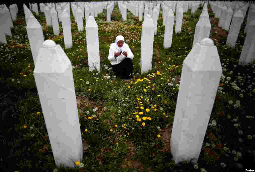 Mejra Dzogaz prays near the graves of her family members at the Memorial Center in Potocari, Bosnia-Herzegovina. (Reuters/Dado Ruvic)