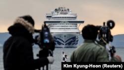 Японские журналисты в порту Йокогамы, впереди — лайнер Diamond Princess. 6 февраля 2020 года.