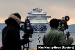 Японские журналисты в порту Иокогамы, впереди - лайнер Diamond Princess. 6 февраля 2020 года