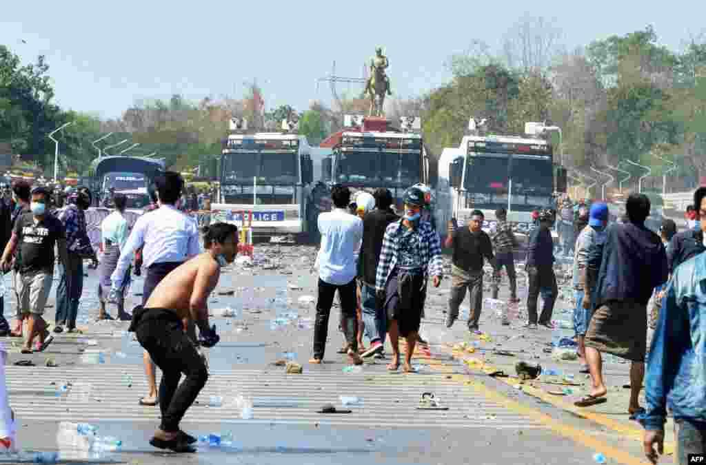 معترضان در نایپیداو پایتخت برما با موترهای پولیس مقابله میکنند. پولس برای متفرق کردن معترضان از توپهای آبپاش استفاده کرد. تظاهرات در برما پس از کودتای نظامی که در نتیجه آن آنگ سان سوچی رهبر این کشور زندانی شد، آغاز گردید. در این عکس معترضان در بنای یادبود جنرال آنگ سان (سی)، پدر فقید رهبر بازداشت شده میانمار (برما)، در نایپیداو پایتخت این کشور قرار دارند. 9 فبروری 2021. (عکس از STR / AFP)