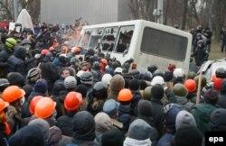 Шерушілер полиция көлігін қиратып жатыр. Киев, 19 қаңтар 2014 жыл.