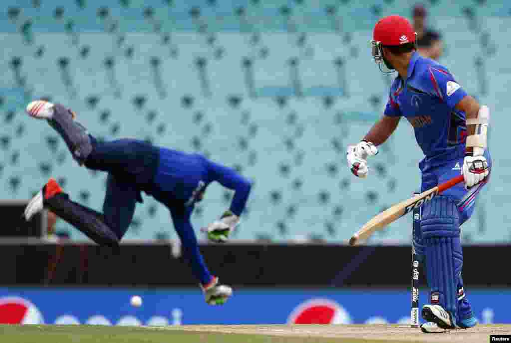 Afghanistan's Nawroz Mangal (right) watches as England's wicketkeeper Jos Buttler unsuccessfully tries to stop a boundary during their Cricket World Cup match in Sydney on March 13. (Reuters/David Gray)
