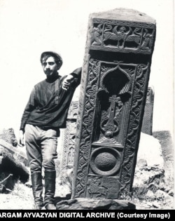 A man leans on a khachkar topped with a winged creature in the Julfa cemetery in 1915.