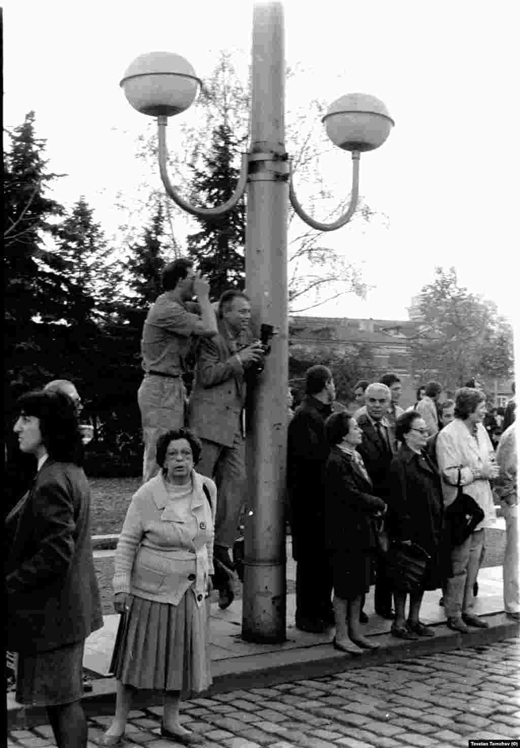 """Двама от фотографите, снимали шествието на """"Екогласност"""" на 3 ноември 1989 г. Усмихнатият вдясно е Стефан Тихов. Много хора не взимат участие в шествието, а го наблюдават отстрани. Осветителните тела на площада са монтирани през 80-те години."""