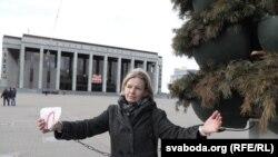 Актывістка Алена Талстая прыкавала сябе да слупу на Кастрычніцкай плошчы ў Менску