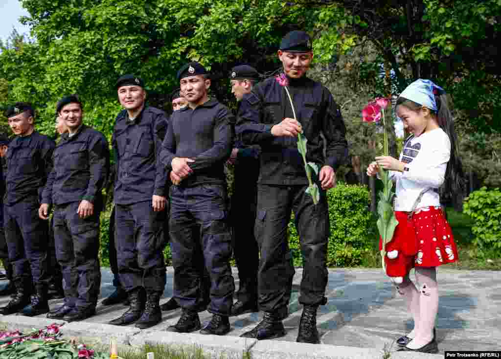 A girl gives a flower to a police officer during a protest in Almaty on the Day of Unity of the People of Kazakhstan in Almaty on May 1. (Pyotr Trotsenko, RFE/RL)