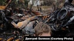 Восточная Украина. Новоалексеевка. Подросток на фоне подорванного грузовика и своего разрушенного дома