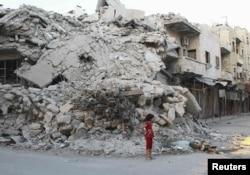Бомба түсіп қираған үйдің қасында тұрған қыз. Сирия, 8 қыркүйек 2013 жыл.