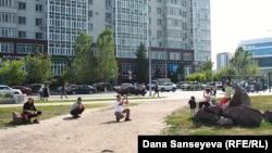 Люди фотографируются на фоне городского пейзажа в Астане.
