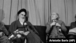 Ayatollah Khomeini, left, announces that Mehdi Bazargan leader of FMI, right, is the new prime minister of his provisional government in Tehran, Feb. 5, 1979.